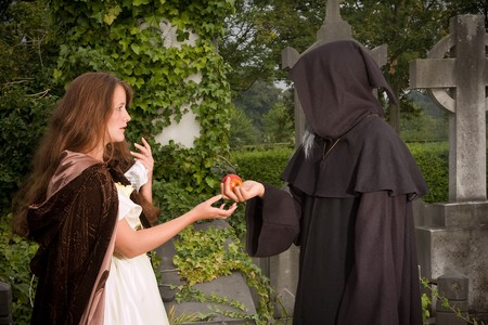 Halloween scene of an evil monk offering an apple  photo