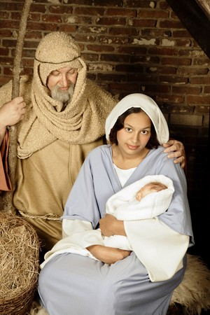 religious holiday: Live Christmas nativity scene reenacted in a medieval barn Stock Photo