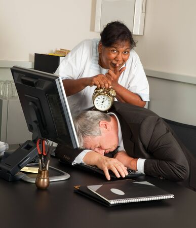 Cleaning woman holding an alarm clock next to a sleeping office worker photo