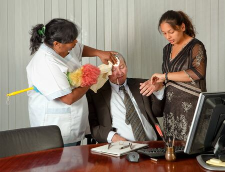Secretary and cleaning woman taking care of the office manager with a fever Stock Photo - 7795469