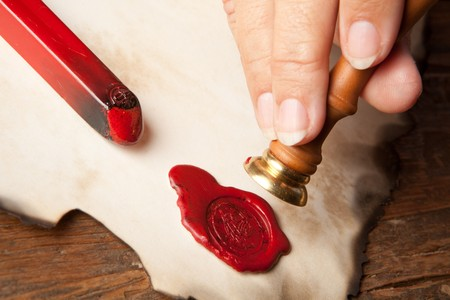 red seal: Hand with ancient parchment or diploma scroll with wax seal Stock Photo