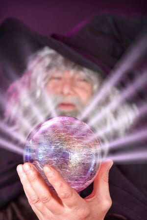 psychic reading: Evil wizard looking into his magic sphere Stock Photo