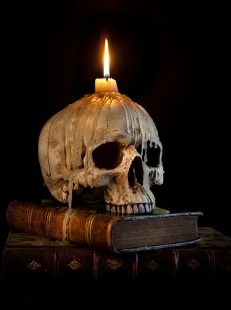 thriller: Halloween image with a burning candle on an ancient skull