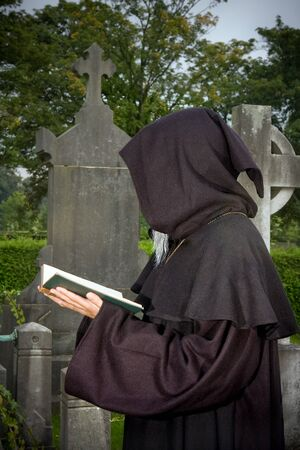 Halloween scene of a black hooded monk praying in a cemetery photo