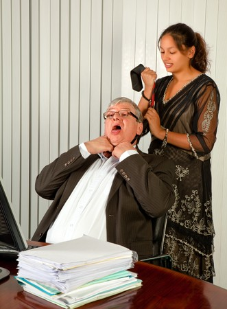 strangling: Office worker or secretary strangling her boss with his own tie Stock Photo