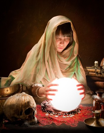palmistry: Young fortune-teller reading the future in a crystral ball