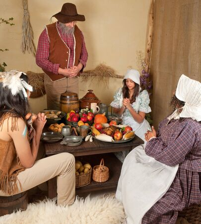Reenactment scene of the first Thanksgiving Dinner in Plymouth in 1621 with a Pilgrim family and a Wampanoag Indian Stock Photo - 7907374