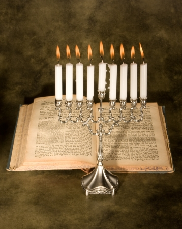 Nine candle menorah and an antique jewish prayer book photo