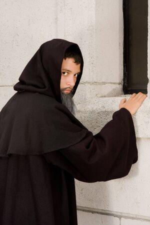 Halloween scene of a creepy black hooded monk photo