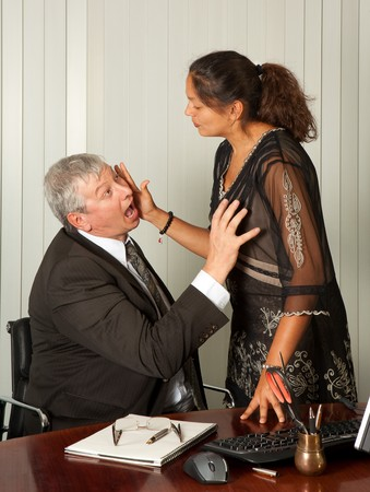 closeness: Secretary defending herself with her scissors against intimacy by her boss Stock Photo