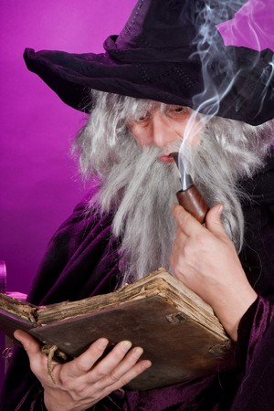 Old sorceror reading a book and smoking a pipe photo