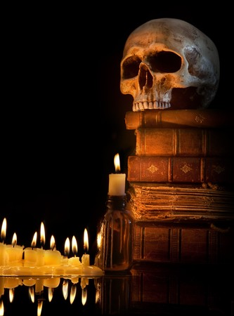 Halloween border with skull, ancient books and candles photo