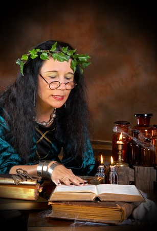 Halloween witch reading in her book of shadows photo