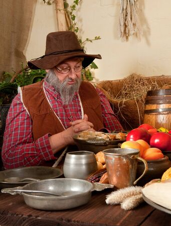 Reenactment scene of the first Thanksgiving Dinner in Plymouth in 1621 with a Pilgrim family and a Wampanoag Indian Stock Photo - 7914330