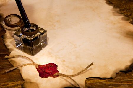 Old ink pot on a parchment scroll with wax seal photo