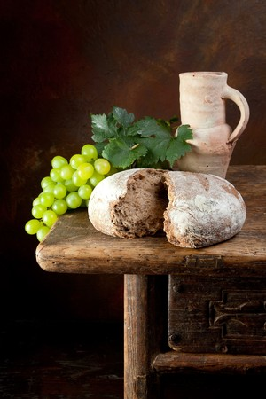Antique wine jug with grapes and holy bread photo