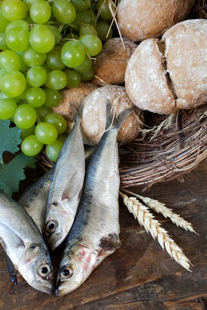 Bread and fish with wine grapes symbolizing the miracles of Jesus Christ Stock Photo - 8107253