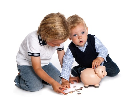 playing with money: Two toddler brothers playing with money and their pink piggy bank Stock Photo