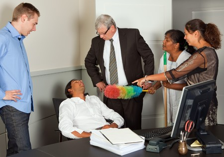 Employees having caught a colleague sleeping at his desk photo