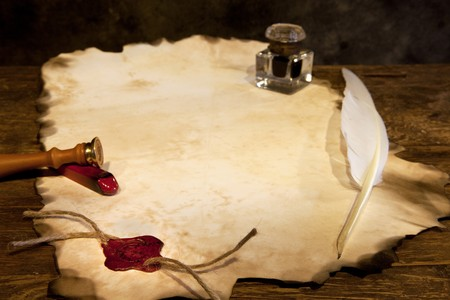 Blank parchment scroll with wax seal and feather quill photo