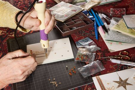 Hands of a woman crafting and scrap-booking christmas cards photo