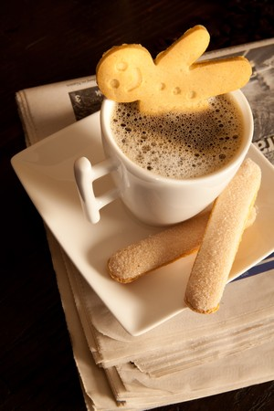 Gingerbread men cookie biscuits with hot coffee on folded newspapers photo