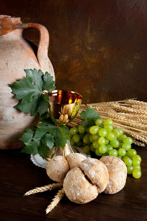 Grapes and holy bread next to a golden chalice with wine photo