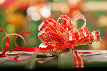 wrapped present: Beautiful christmas present against a background of blurred christmas lights Stock Photo