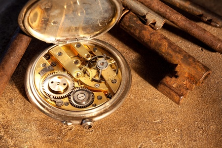Rusty keys and an antique pocket watch on a grunge background photo