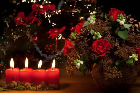 christmas flower: Christmas candles, flower arrangement and blurred christmas tree Stock Photo
