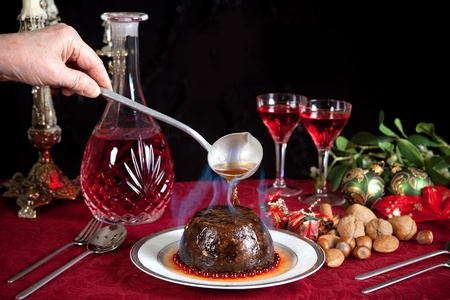 plum pudding: Hand serving burning brandy over a christmas or plum pudding