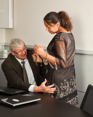 sexual woman: Secretary defending herself with her scissors against intimacy by her boss Stock Photo