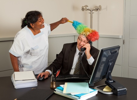 Funny cleaning woman cleaning the office of the manager including his face Stock Photo - 8419471