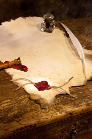 Empty parchment scroll with wax seal and feather quill photo