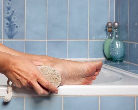 removing: Hand removing callus from feet using pumice stone