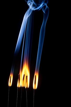 Incense burning with beautiful smoke fumes and wisps photo