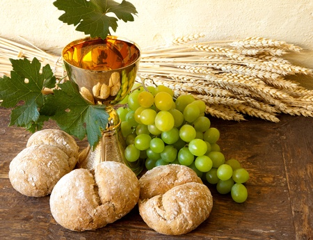 Grapes and holy bread next to a golden chalice with wine Stock Photo - 8489217