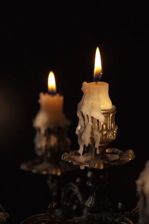 candlestick: Bronze antique candlestick with burning candles in darkness Stock Photo