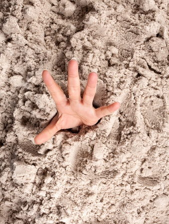 sinking: Hand on a beach sinking or drowning in quicksand