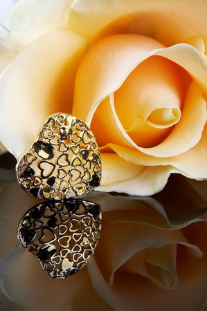Gorgeous yellow rose and a golden heart on a reflective surface photo