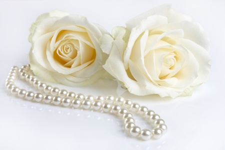 woman in white: Symphony in white, two white roses and a pearl necklace, as a valentine gift Stock Photo