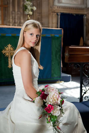 Young blonde bride posing in a medieval English church photo