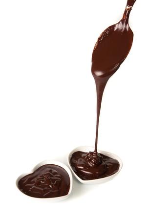 chocolate melt: Versando il cioccolato in due tazze di forma del cuore di pietra per il giorno di San Valentino Archivio Fotografico