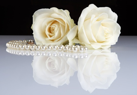 Two white roses reflected on a white surface, and a pearl necklace photo