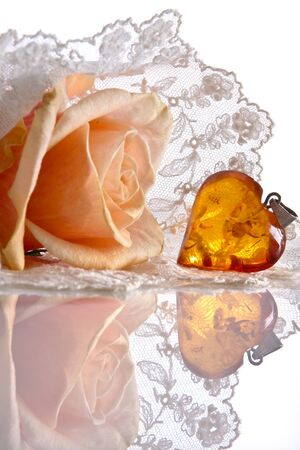 Amber heart and roses lying on a lace veil;  photo