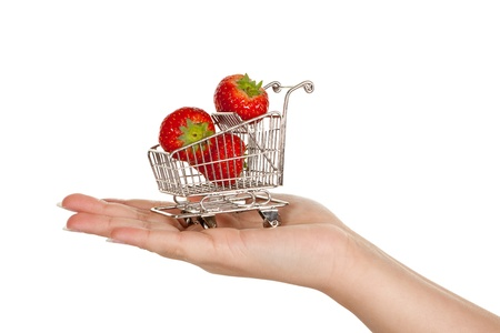 Female hand carrying a miniature shopping trolley with strawberries photo