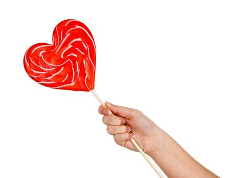 Female hand holding a very large heart-shaped lolly photo
