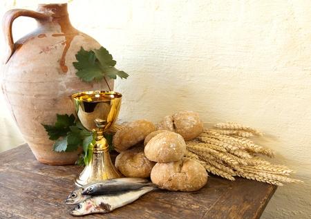 comunion: Pan y pescado con una jarra de vino antiguo que simboliza los milagros de Jes�s Cristo Foto de archivo