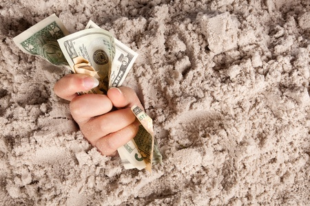 sinking: Female hand drowning in quicksand holding banknotes or money Stock Photo
