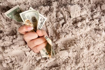 Mano femmina annegamento in sabbie holding banconote o denaro